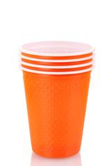 Bright orange plastic cups isolated on white