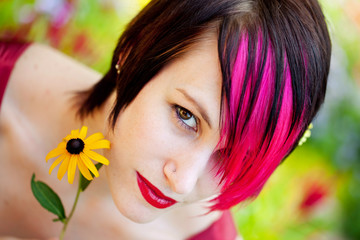 Beautiful punk woman with pink hair in the garden
