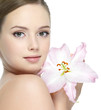 Beautiful face of young girl with flower - isolated