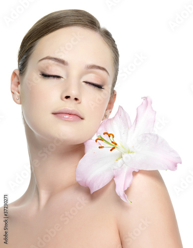 Beautiful young girl with flower on shoulder - isolated