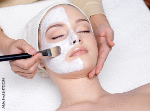 Woman having a facial cosmetic mask
