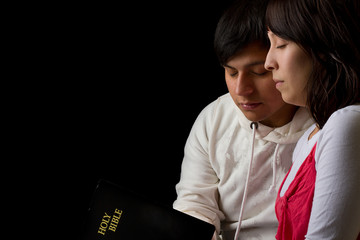 Hispanic Couple Studying the Bible and Praying