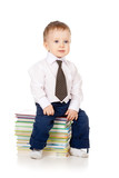 toddler dressed in suit and sitting on the heap of books