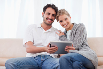 Charming couple using a tablet computer