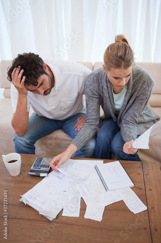 Portrait of a depressed couple doing their accounting