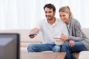 Smiling couple watching TV while eating popcorn