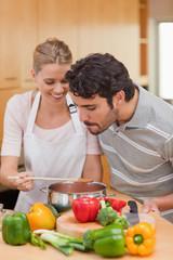 Portrait of a happy couple preparing a sauce
