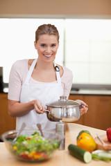 Portrait of a woman holding a sauce pan