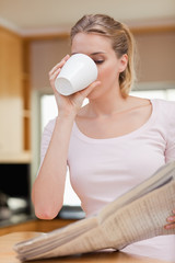 Portrait of a young woman reading the news while having tea