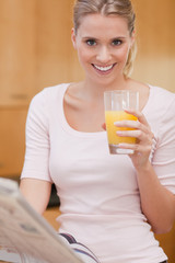 Portrait of a cute woman reading the news while drinking juice