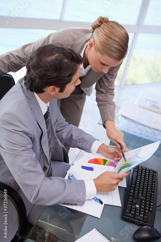 Portrait of a manager pointing at something to her employee on a