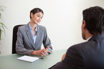 Manager interviewing a good looking applicant