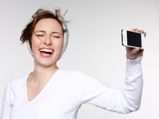 Laughing girl takes a self-photograph with smart phone