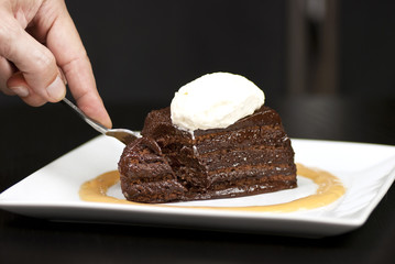 Hand Holding Fork Slicing Into A Chocolate Marquise With White C