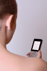A young girl is holding a cell phone.