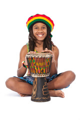 rasta man sitting on the floor and beat a drum