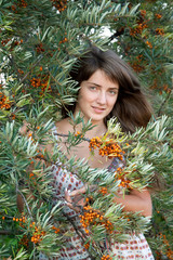 woman in seabuckthorn plant