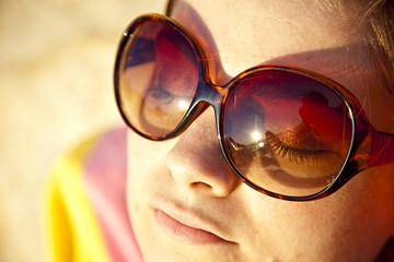 femme a lunettes de soleil bronze sur la plage