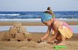The child builds a sand castle on the beach