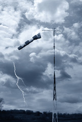 wind direction indicator under cloudy sky with lightning