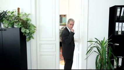 Ein Mann in einem Büro fordert zum Schweigen auf