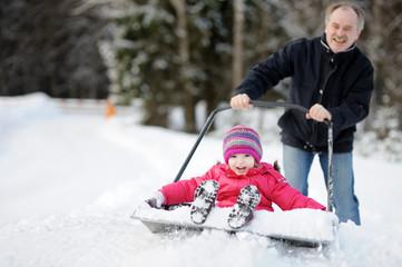 Winter fun: little girl having a ride on a snow shovel