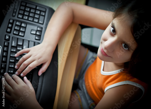 Small girl working with a computer at home