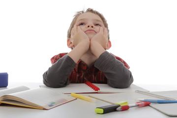 enfant graçon rêvant au lieu de faire ses devoirs