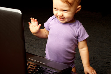 Happy baby laughing at laptop screen