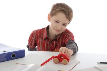 garçon enfant jouant pendant ses devoirs