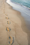 Foot imprints beside waves reaching margin. Romantic stroll. poster