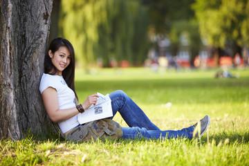 Mädchen sitzt unter Baum, lernen