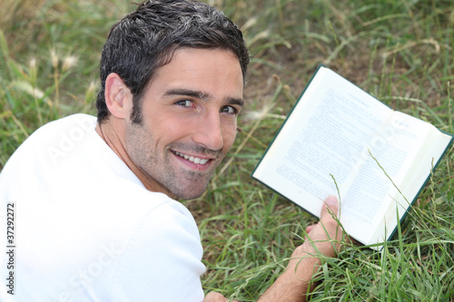 a man lying on grass is reading a book