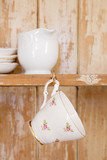 tea cup hanging on a hook in old wooden cupboard poster