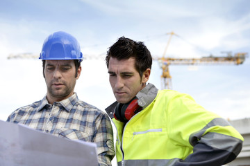 two supervisors on a construction site looking at a blueprint
