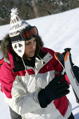 Young woman looking at her skis
