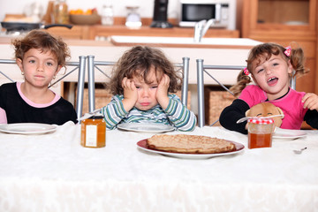three children eating crepes