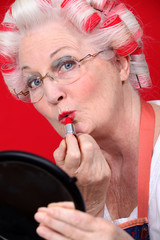 grandmother with hair curlers putting on lipstick