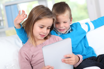 Children using electronic tablet at home