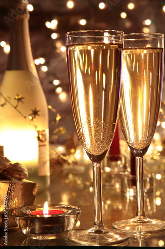 Closeup of champagne in glasses and bottle .