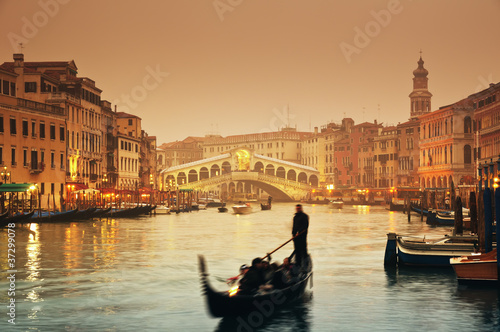 Leinwanddruck Bild Rialto Bridge and gondolas at a foggy autumn evening in Venice.
