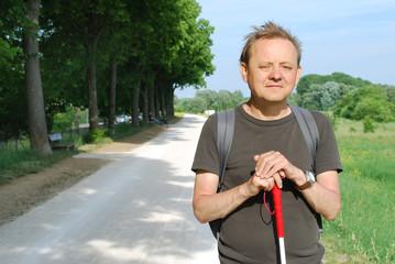 Blinder Mann mit Blindenstock unterwegs im Freien