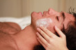 Facial massage to a relaxed young man at the spa