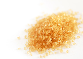heap of yellowish brown sugar over white background