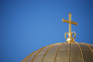 Golden orthodox cross and dome close-up on blue-sky background