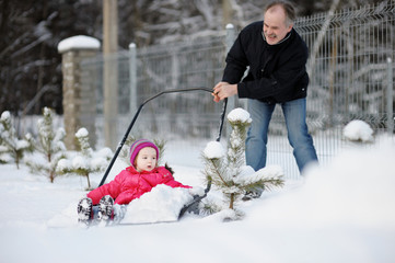 Winter fun: little girl having a ride on a snow shovel