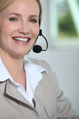 Woman laughing with headset.
