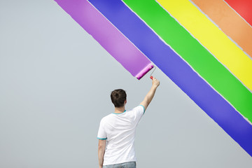 young man painting rainbow