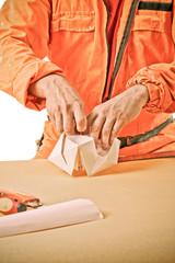 workman's hands make paper ship