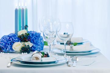 Gedeckter Tisch mit blauen Kerzen
